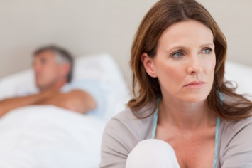 Sad woman sitting up in bed while husband sleeps