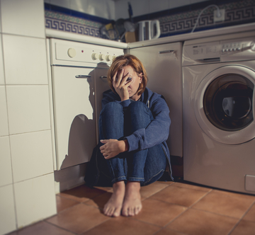 Depressed woman sitting on kitchen floor
