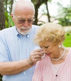 Elderly man wiping away the tears from an elderly woman
