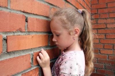 Sad little girl facing a brick wall