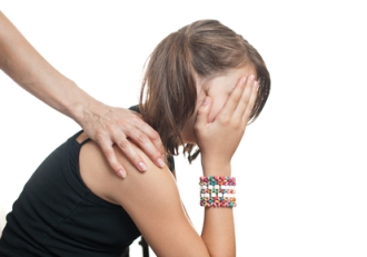 Sad young woman being consoled by another person's hand on her shoulder